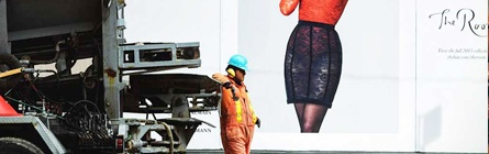 Construction worker in front of boutique sign